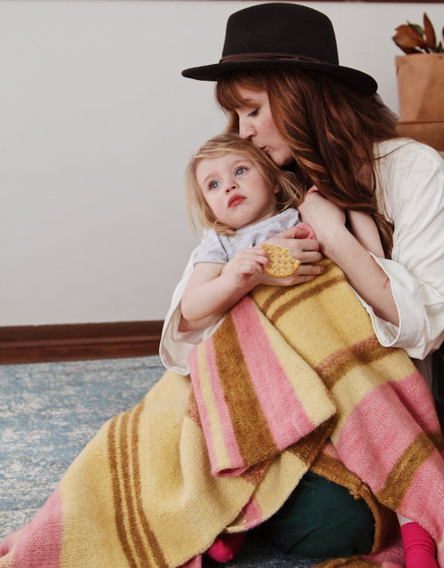Laura Kirkpatrick of America's Next Top Model at home with her daughter Willow, wrapped up in a Storyteller alpaca knit throw