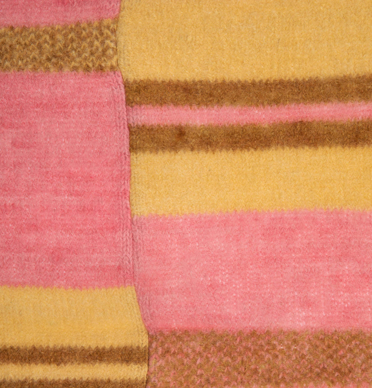 closeup of pattern on pink yellow and brown Alpaca blanket knitted by storyteller studio