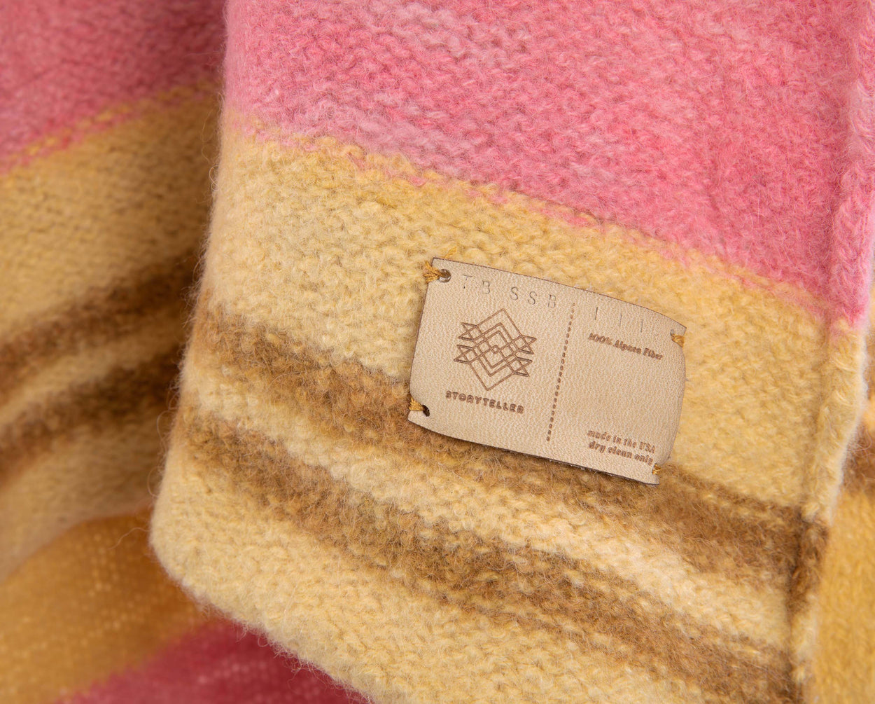 closeup of label on pink yellow and brown Alpaca blanket knitted by storyteller studio