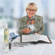 Mature woman using ERGO Lux magnifier to read menu