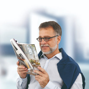mature man wearing improvision spectacles reading magazine