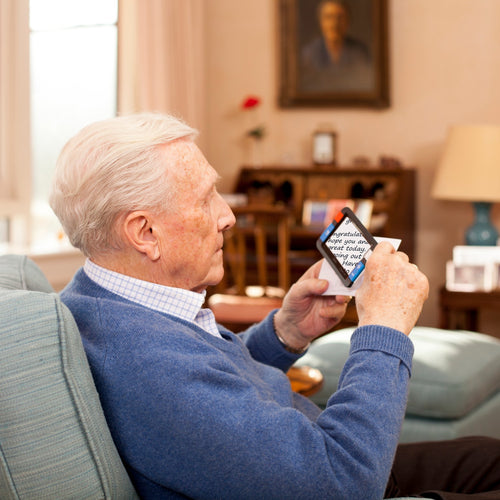 senior using compact plus to magnify and read postcard