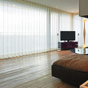 Bedroom scene with wooden flooring and gorgeous track system blinds.