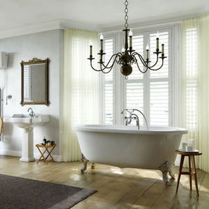 Beautiful bathroom scene with white shutters custom made for the window alcove.