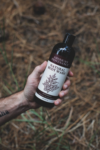 Man holding American Provenance Natural Body Wash in Patchouli Scent over grass