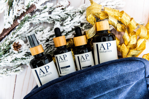 AP Botanics Skincare products sticking out of a canvas dopp kit with holiday decor in the background