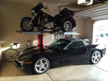 Single-post vehicle lift holding a motorcycle above a Corvette in a residential garage