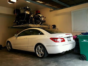 Single-post vehicle lift holding both a motorcycle and a moped over a Mercedes for extra space in a home garage