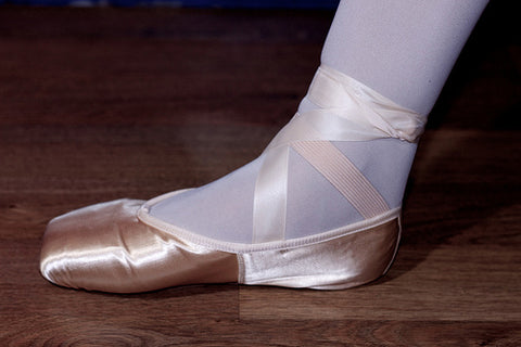 Pointe shoe with ribbon and elastic sewn