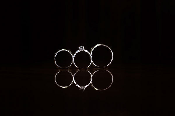 Three silver engagement rings lined up against an all-black background