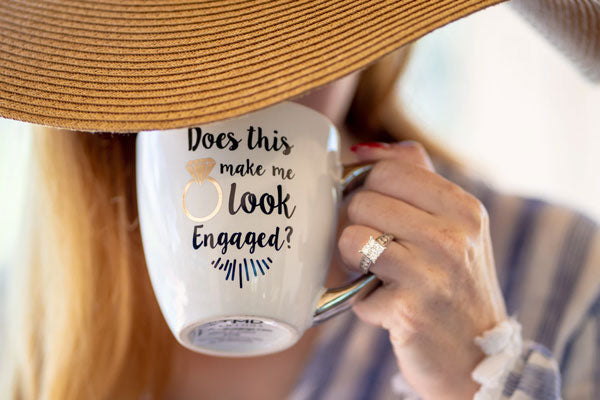 Woman with large engagement ring sips from a coffee mug