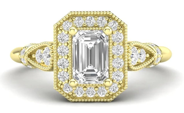 A yellow gold and emerald cut diamond ring