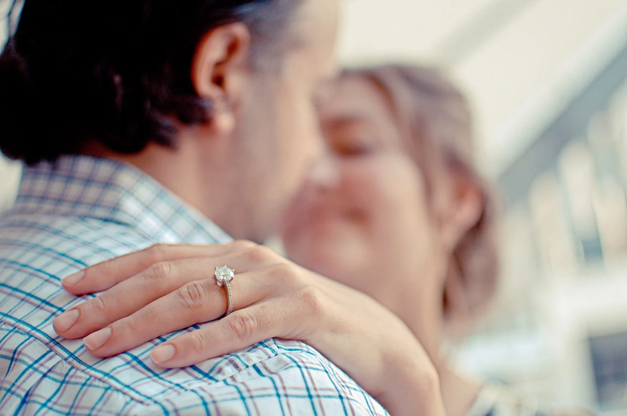 happy couple with an engagement ring in the front