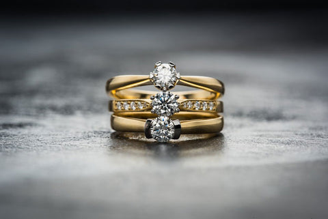 A stack of three yellow-gold diamond rings.