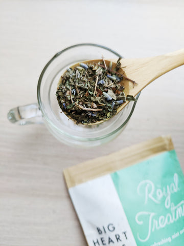 Preparing loose leaf Royal Treatmint by Big Heart Tea Co., with a wooden spoon and glass teapot
