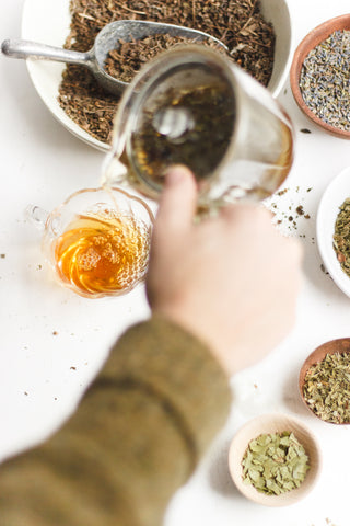 A hand pouring brewed herbal tea Royal Treatmint into a glass cup, surrounded by bowls with the raw, organic ingredients Big Heart Tea Co. uses to blend