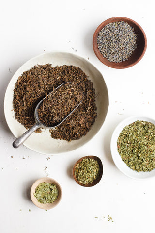 A collection of bowls filled with the raw, organic herbal ingredients for Big Heart Tea Co.'s Royal Treatmint: tulsi, lavender, spearmint, peppermint, and ginkgo.