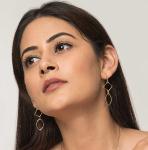 Woman wearing golden brass ethical jewellery earrings. Sold in UK.
