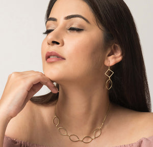 Fairtrade jewellery. Handmade jewellery of golden brass earrings and necklace with geometric shapes
