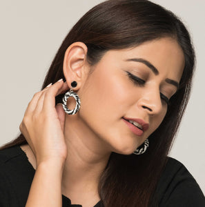 Women wearing ethical jewellery. Handmade drop ring earrings of black and white swirls.
