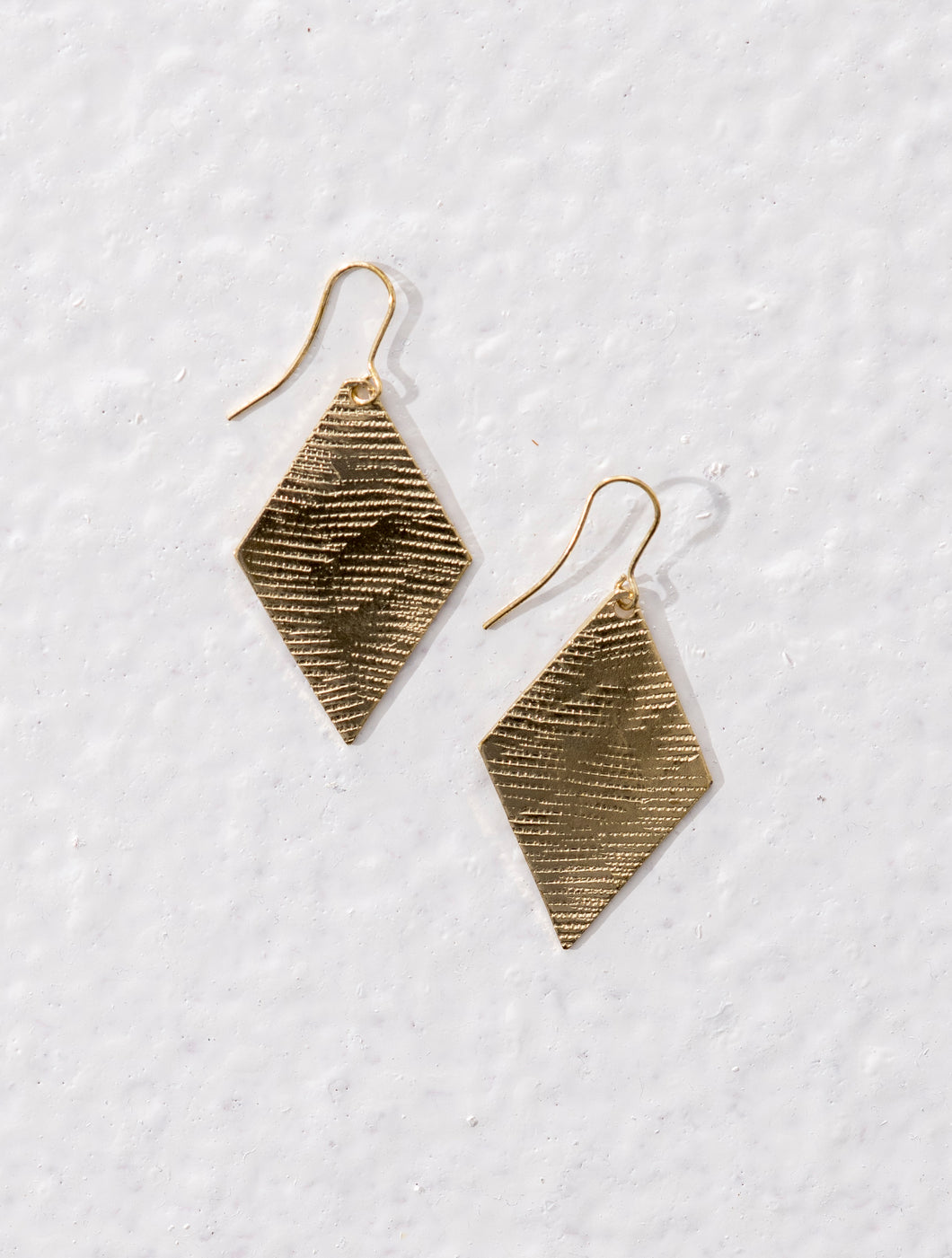 Diamond shaped ethical jewellery drop earrings made of brass with rough textured effect.