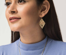 Woman wearing golden drop earrings that are diamond shaped with rough textured effect. Fair trade.