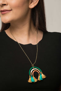 Woman wearing fairtrade brass necklace. Pendant is rainbow-like and has tassels. Sustainable fashion