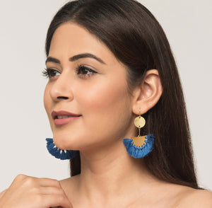 Woman wearing statement golden fair trade earrings with royal blue tassels Made of brass. Ethical.