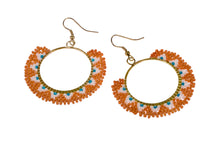 Intricately constructred piece of ethical jewellery. Colourful earrings made of orange glass beads.