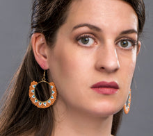 Woman wearing ring shaped drop earrings made of orange, blue, white glass beads. Ethical jewelry.