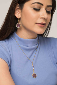 Woman wearing reversible ethical jewellery. Earring and necklace set with purple and white sides.
