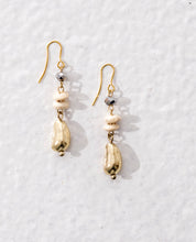 Long drop earrings made of irregular shaped golden metal beads and small white wooden beads. Vegan.