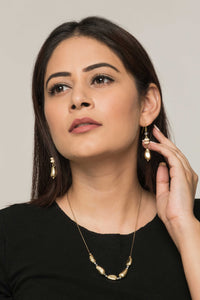 Woman wearing set of sustainable fashion necklace and earrings with oddly shaped golden metal beads.