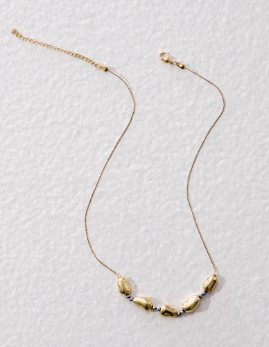 Handmade fair trade necklace with irregular shaped golden metal beads. Ethically made in India. .