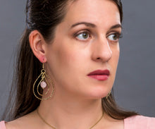 Woman wearing ethical drop earrings with sustainable pink stone in golden concentric teardrops.