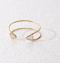 Open ended adjustable ethical bracelet made of golden brass and finished with white triangular tips.