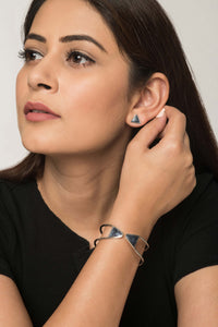 Woman wearing triangular grey and silver stud earrings and silver brass bracelet with grey tips.