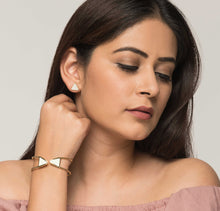 Woman wearing triangular white and golden stud earrings and brass bracelet with white enamel tips.