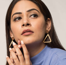 Woman wearing hollow triangular earrings made with natural fibres and wood. Eco-friendly and vegan.