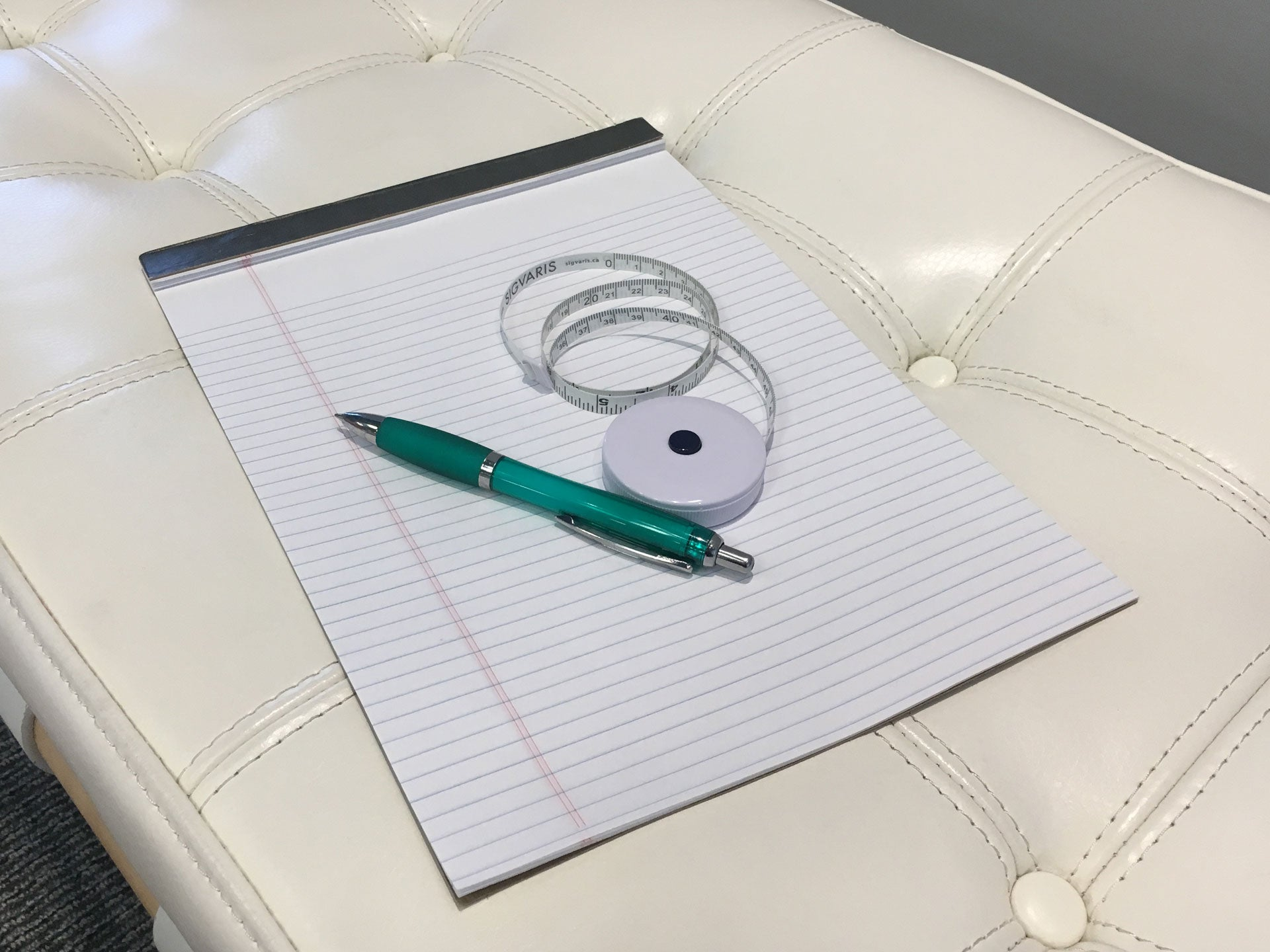 Pen notepad and measuring tape use for taking measurements for compression stockings