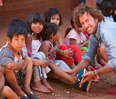 118836c2841 Blake Mycoskie putting a shoe on a young hispanic child s foot sitting on  the ground among