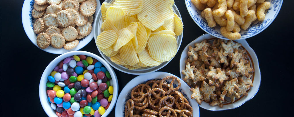 Dishes of candy, chips, and other processed foods