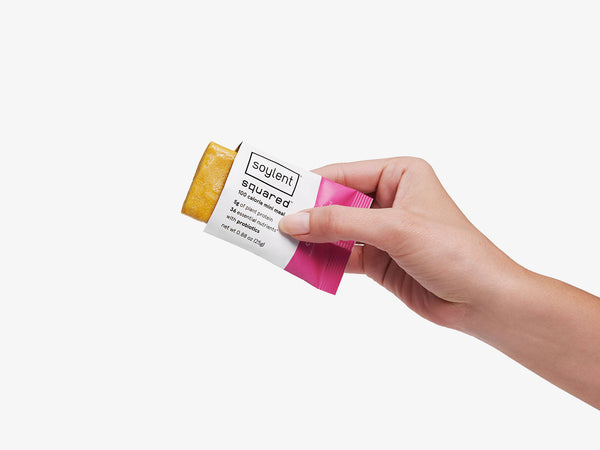 women hand holding a citrus berry soylent squared bar