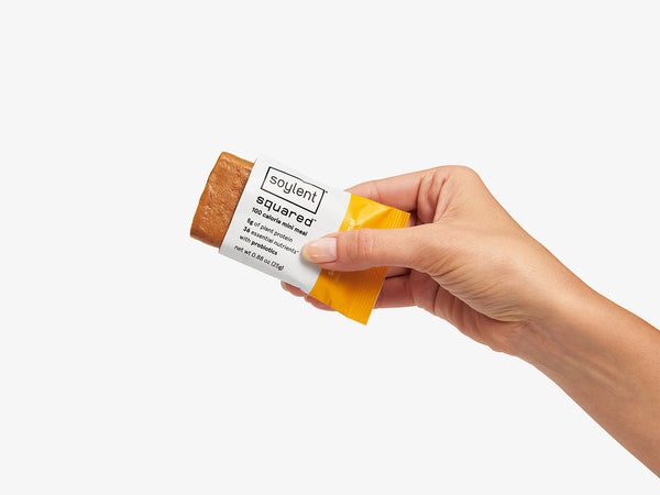 women hand holding a slated caramel soylent squared bar