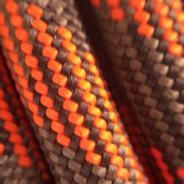closeup of maxim pinnacle slick double dry treated dynamic climbing rope showing 1x1 weave of orange black and gray yarns comprising slick option