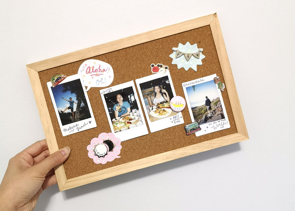 Decorated corkboard with enamel pins and stickers