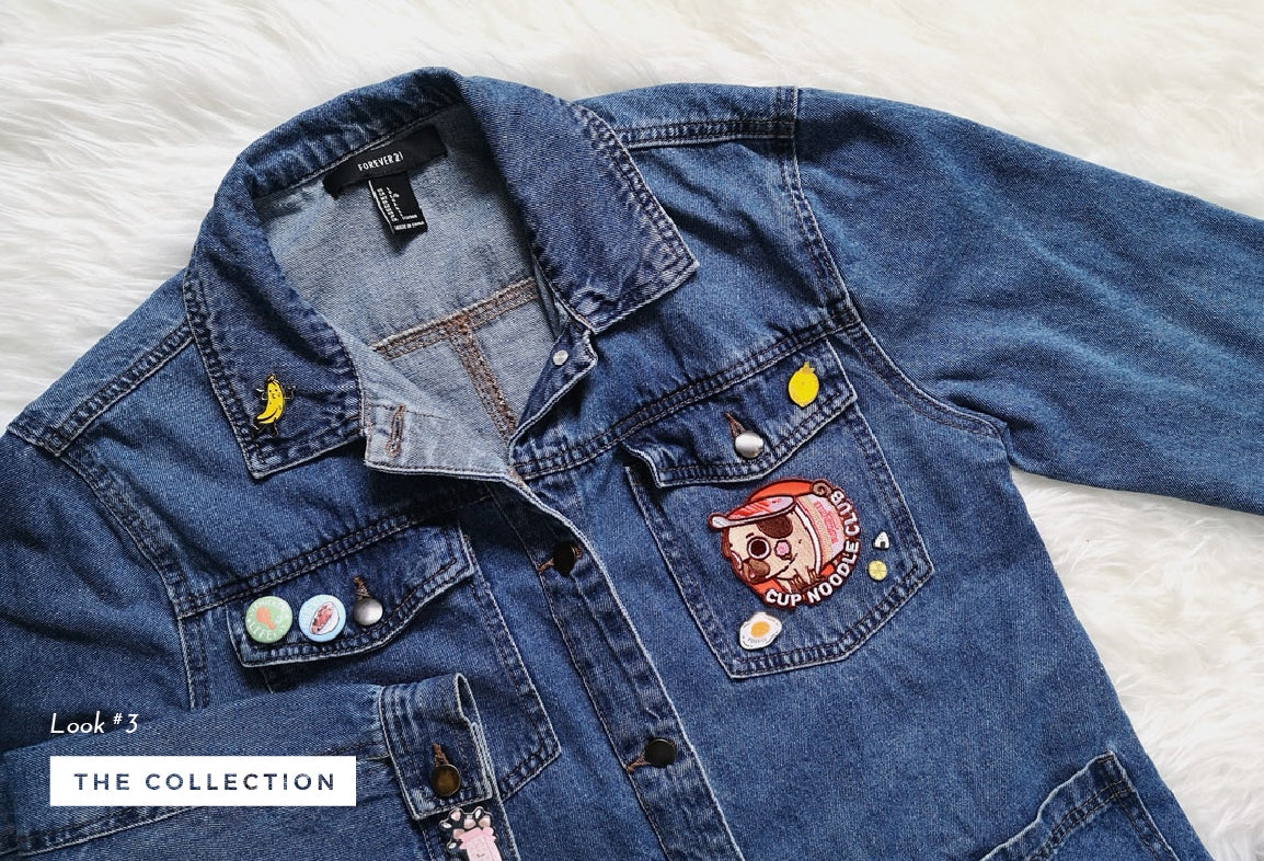 Denim jacket with a collection of food themed enamel pins and patches.