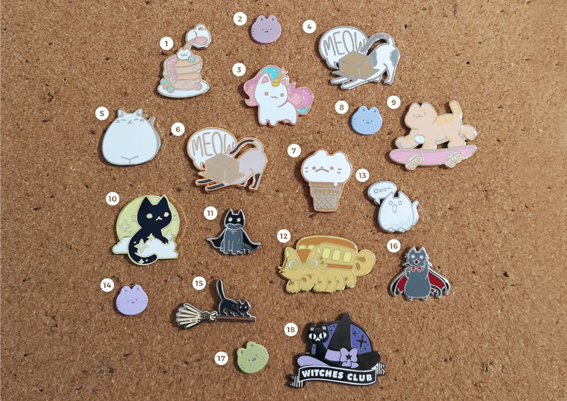 cat enamel pins collection on pin board