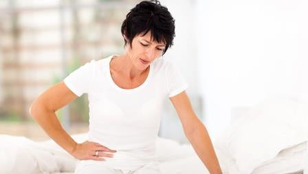 Middle aged female sitting on bed Not feeling well