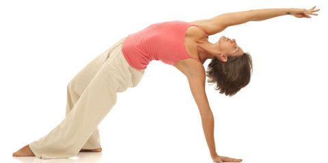 Female doing backward yoga bend white background